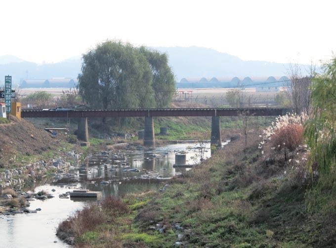 수인선 협궤철도의 흔적이 남은 오목천 부근. 멀리 수원공군비행장의 격납고가 보인다.