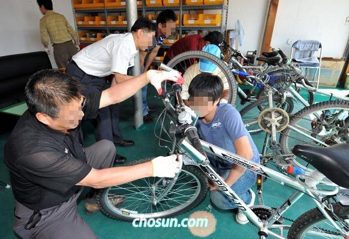 2009년 6월 4일 대구시 서구청 뒤 평리초등학교 인근의 서구 자전거 무료수리 센터에서 희망근로 프로젝트에 참가한 자전거 기술자들이 시민들이 맡긴 고장난 자전거를 수리하고 있다.