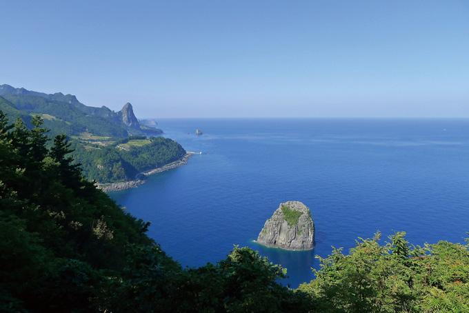 석포일출일몰전망대에서 서쪽으로 본 풍경. 멀리 송곳산이 우뚝하고, 바로 앞에는 딴바위섬이 몽실 떠 있다.