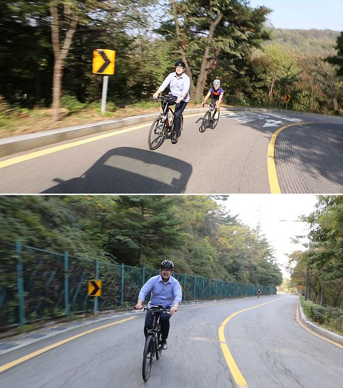 전기자전거를 타고 언덕길을 웃으며 달리는 일반인 라이더의 모습이 인상적이다.
