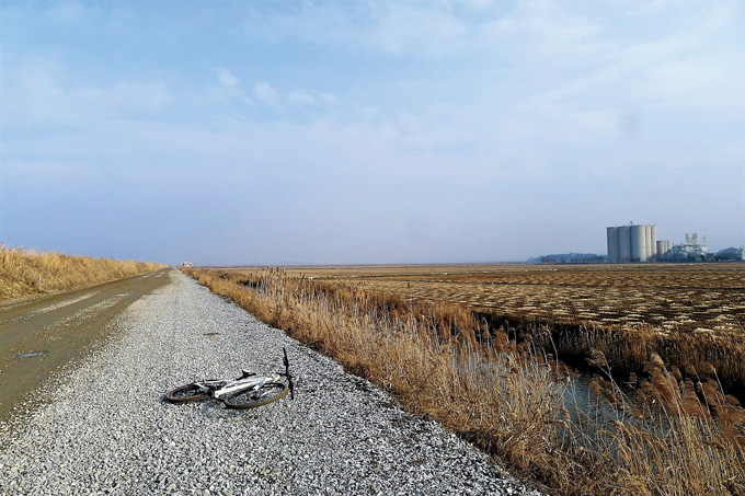나무 한 그루 없는 드넓은 평원에서 대책 없는 자전거는 그 자리에 편히 드러누웠다. 오른쪽에 보이는 건물은 현대 서산농장의 거대한 저장고