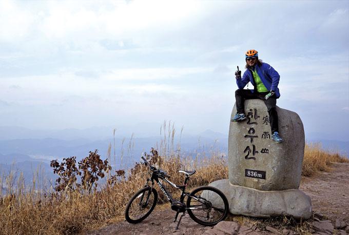 서쪽을 등지고 한우산 정상 표지석에 턱 걸터앉은 이윤기 이사. 대기가 흐려 지리 산은 보이지 않는다. 표지석 옆으로 봉긋한 합천 허굴산(681m)이 보이고, 그 왼쪽으로 희미하게 보이는 높은 산은 산청과 합천 경계의 황매산(1108m)이다.