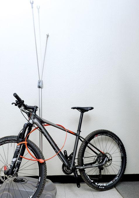 자전거는 자물쇠로 잘 고정되어 있지만, 자전거를 들어 쉽게 빼낼 수 있다.