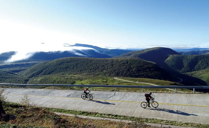 백두산 남쪽 기슭을 올라가는 남파산문 코스로 업힐하는 도중 해발 약 2000m지점에서 남서쪽으로 내려다본 모습. 백두산은 남쪽에 기생화산이 여럿 있어서 협곡과 다소 복잡한 지형을 이룬다. 왼쪽 구름을 인 산은 대규모 기생화산인 망천아봉(2051m)이다.멀리 저지대 기슭에는 구름바다가 하얗다.