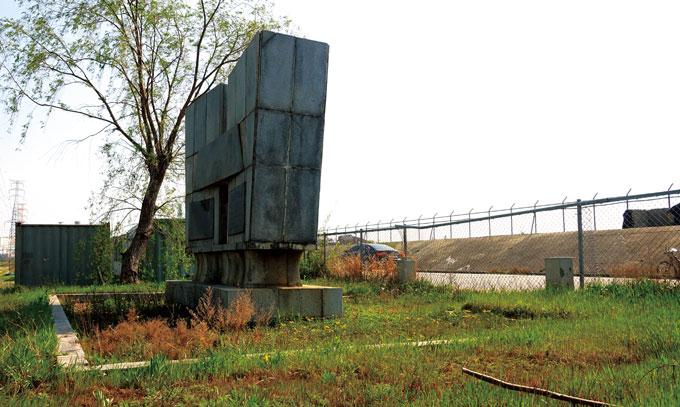 돌보는 이 없이 잡초 속에 방치된 남양방조제 준공기념탑