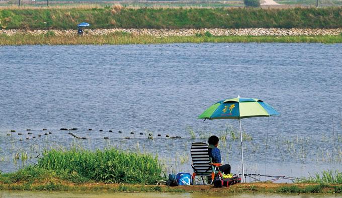 좁 은 호수를 사이로 마주한 낚시꾼. 파라솔 아래 안락의자까지 한없이 평화롭고 편안해 보인다.